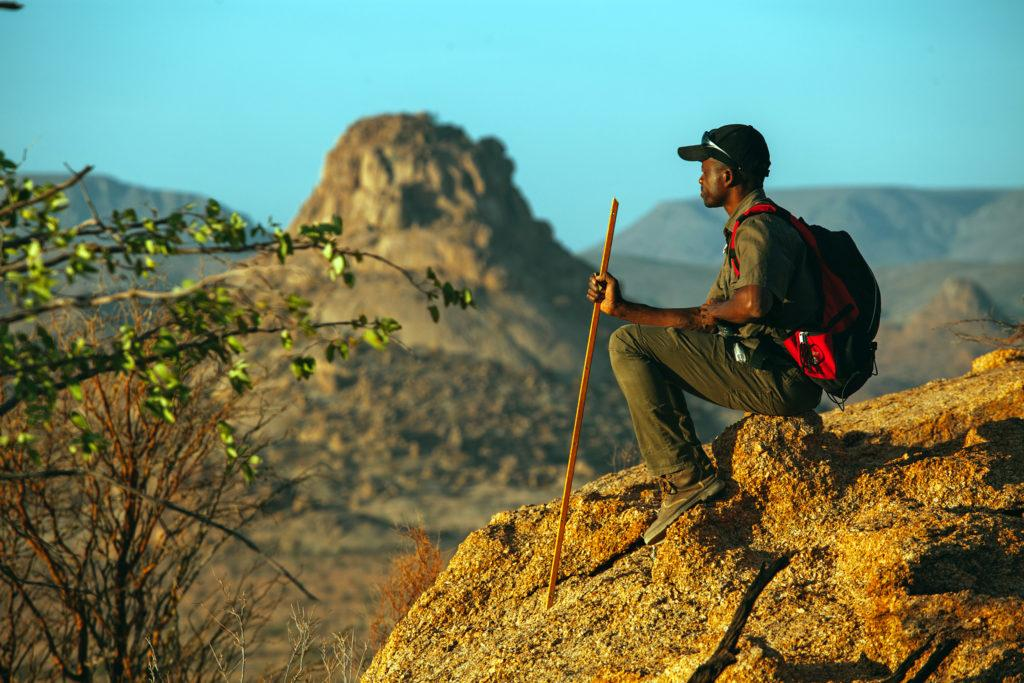 A man wearing a backpack and cap sitting on a rock in Namibia