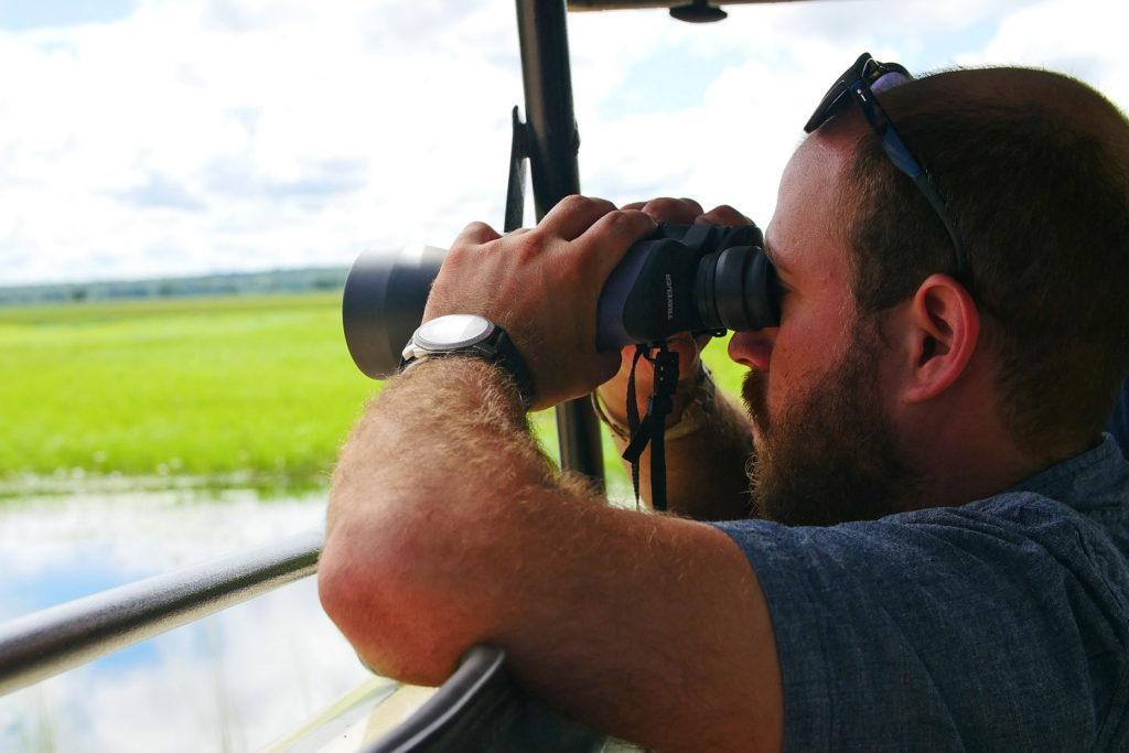 A man looking through binoculars on a game drive