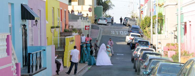 A wedding party with bride and groom in the streets of Bookap in Cape Town, South Africa