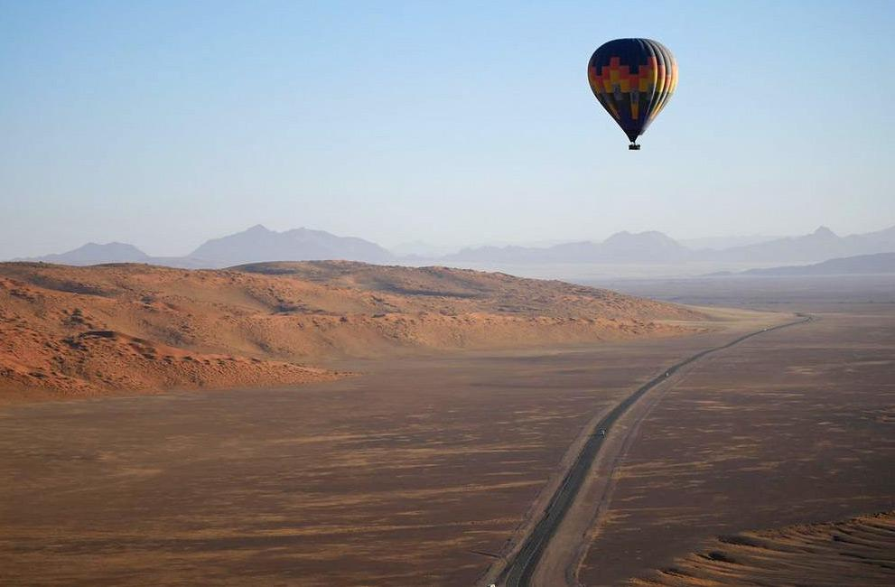 A blue, red, and yellow coloured hot air balloon flies across a straight road in a desert landscape in Namibia