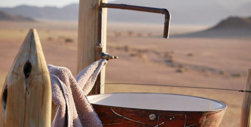 An outdoor wash basin with tap and towel, the Namib desert in the background
