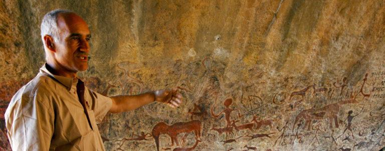 Guide Juan pointing at ancient rock art in Namibia
