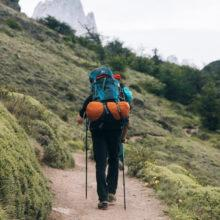 A hiker with a backpack and walking poles hiking along a narrow path