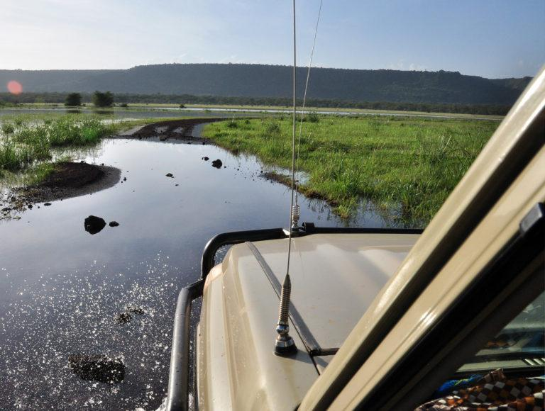 A Land Cruiser driving across a flooded road in Ngorongoro Crater, Tanzania