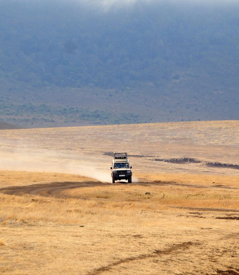 A safari vehicle driving across the caldera of the Ngorongoro Crater