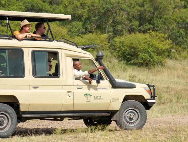 Two travellers looking out of the roof hatch of a safari vehicle, while their guide points in the distance