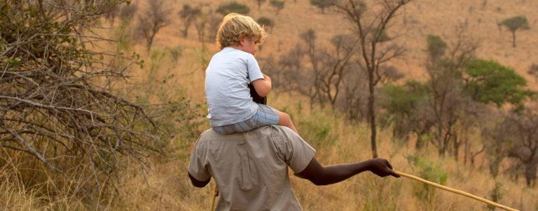 A young child sitting on the shoulders of a man as they explore the area