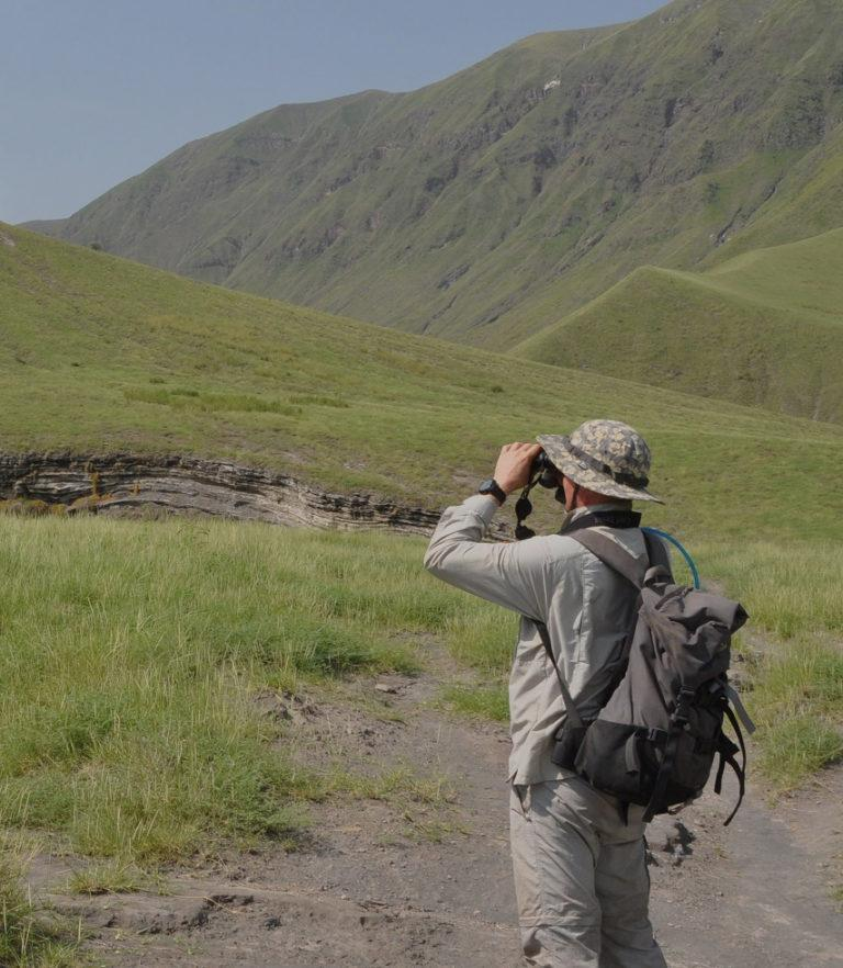A hiker with hat and backpack looking through binoculars, standing in the Ngorongoro Highlands