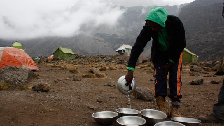 A waiter with a green hoodie on the Barranco Campsite on Kilimanjaro, pours hot water into washing bowls on the ground