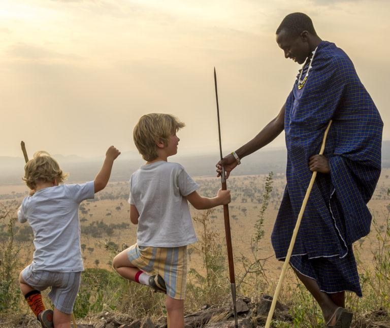 Two young children trying to stand on one leg, while a Masai man assists them