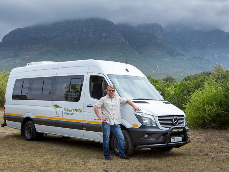 A Mercedes Sprinter tour vehicle with Guide Roy standing next to it in South Africa