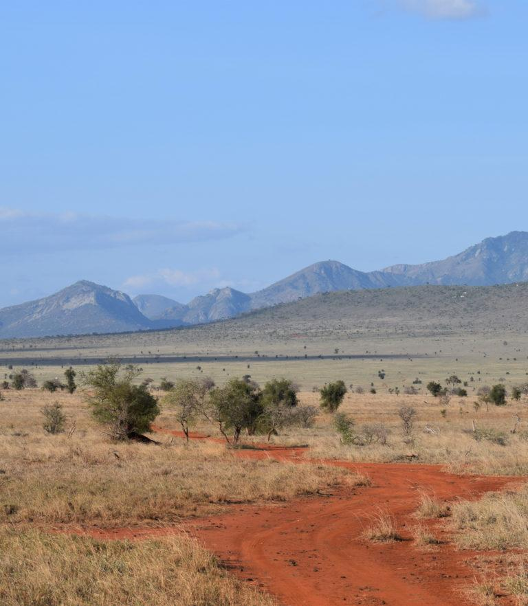 View of a mountainous landscape and red gravel road in Amboseli National Park, Kenya