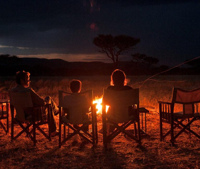 Parents and a child sit on camping chairs around a campfire