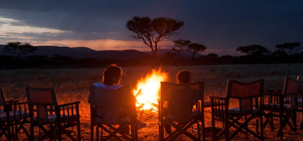 A mother and her child sitting on camping chairs around a campfire at sunset in the Serengeti