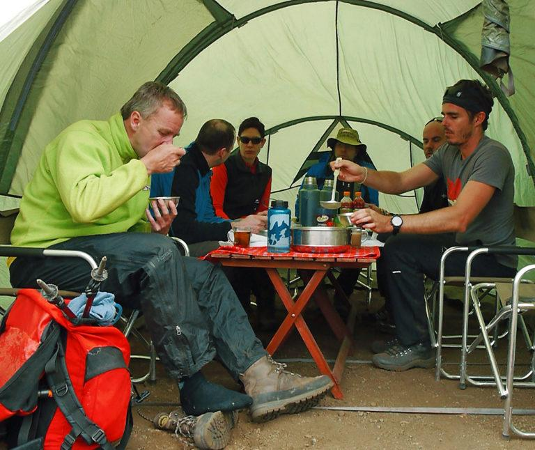 A group of climbers sitting around a table eating, in a mess tent on Mt Kilimanjaro
