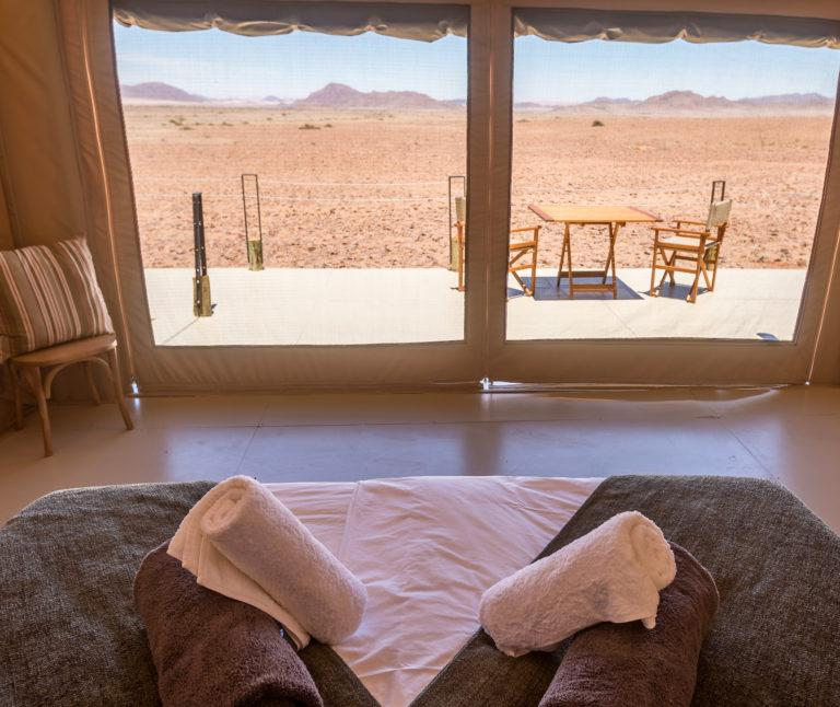 A room with a large window and terrace at Elegant Desert Lodge in Namibia