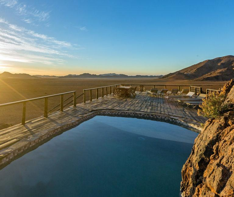 The swimming pool and deck at the Elegant Desert Lodge at sunset