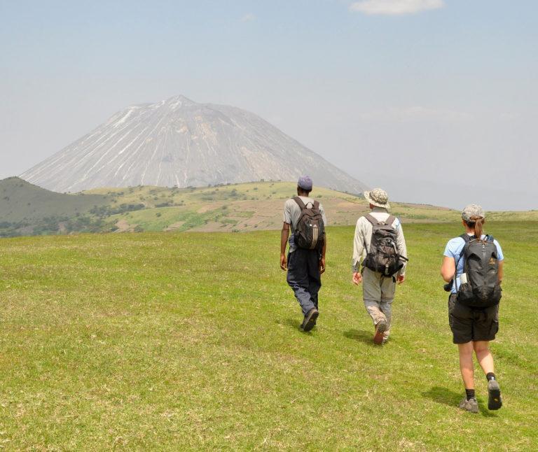 Three people walking uphill towards Ol Doinyo Lengai in Tanzania