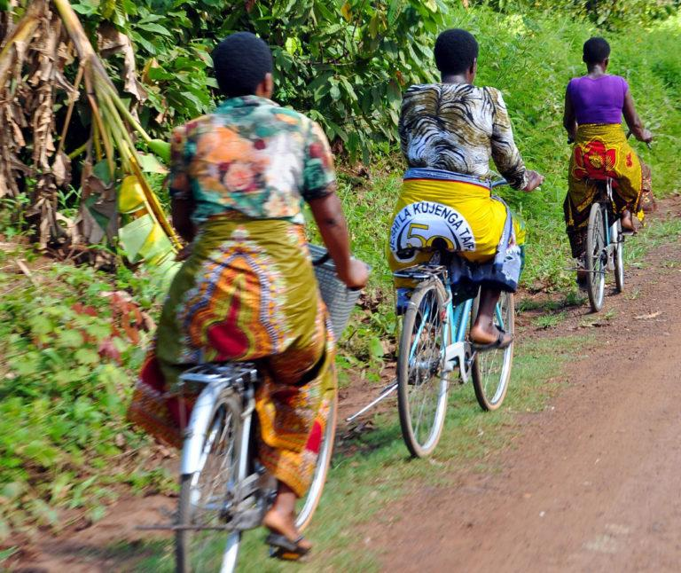 Three women with yellow skirts riding along a road on bycicles