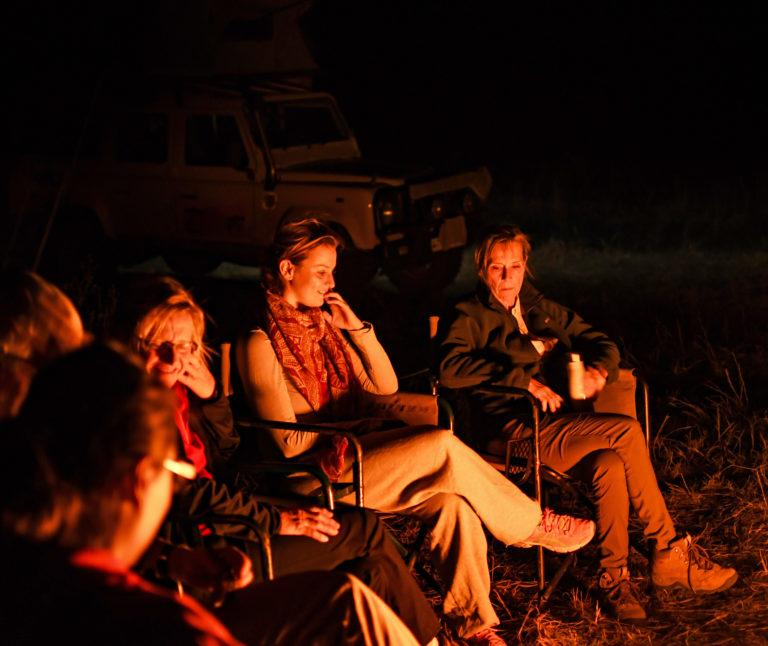 Travellers sitting on camping chairs around a campfire, their faces illuminated by the fire