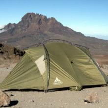 A green Vaude mountain tent on Kilimanjaro with Mawenzi peak in the background