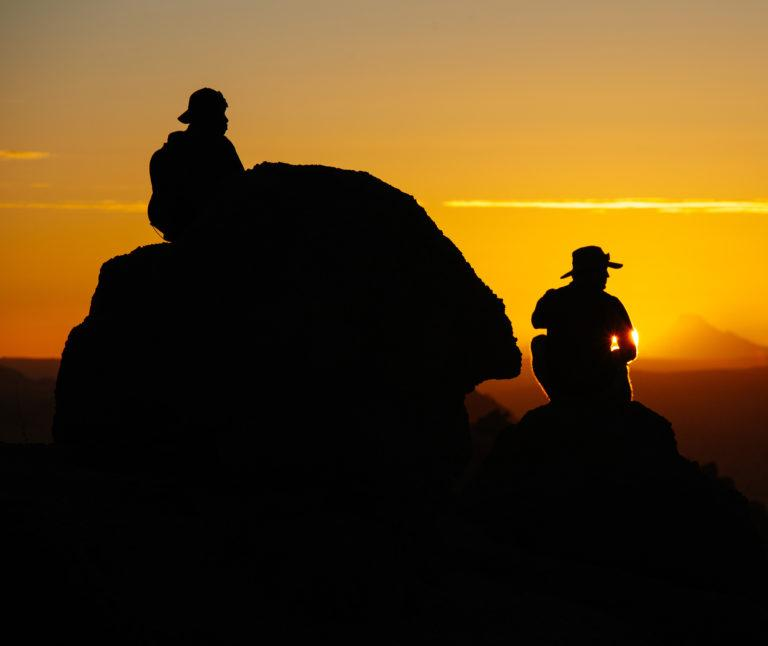 Two hikers sit on rocks as the sun goes down, colouring the sky golden