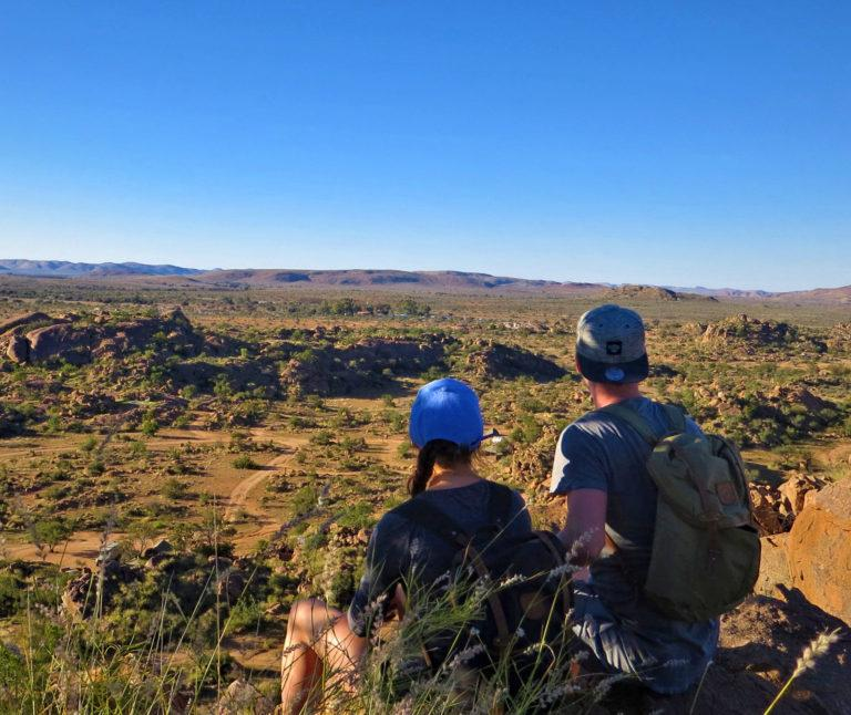 Two hikers wearnig hats overlooking a wide landscape in Namibia