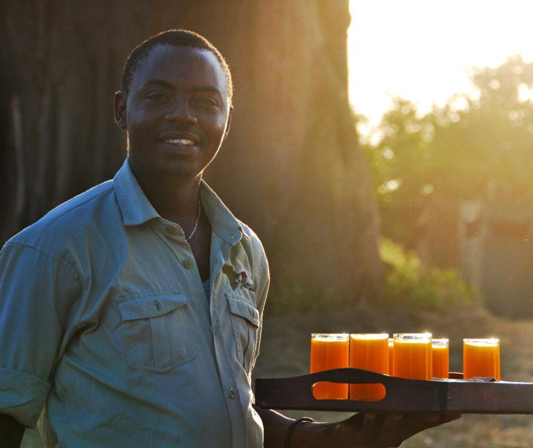 A waiter smiling at the camera while holding a tray with glasses filled with mango juice