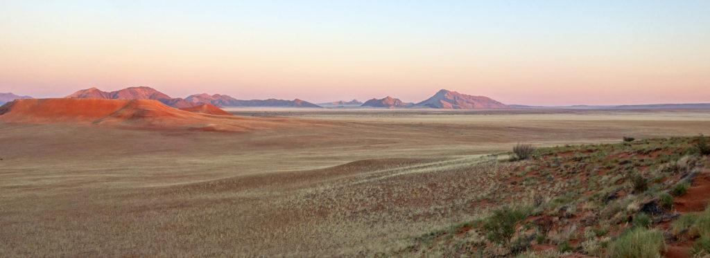 Panoramic view across a wide open landscape at sunset in Namibia