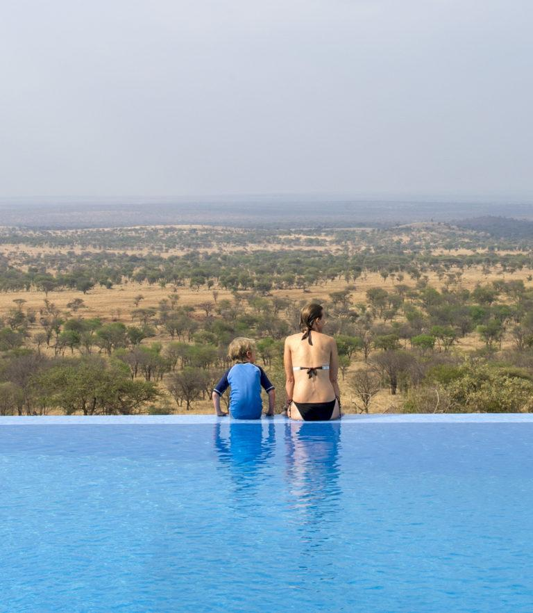 A woman and a child sitting at the edge of a swimming pool overlooking the Tarangire National Park in Tanzania