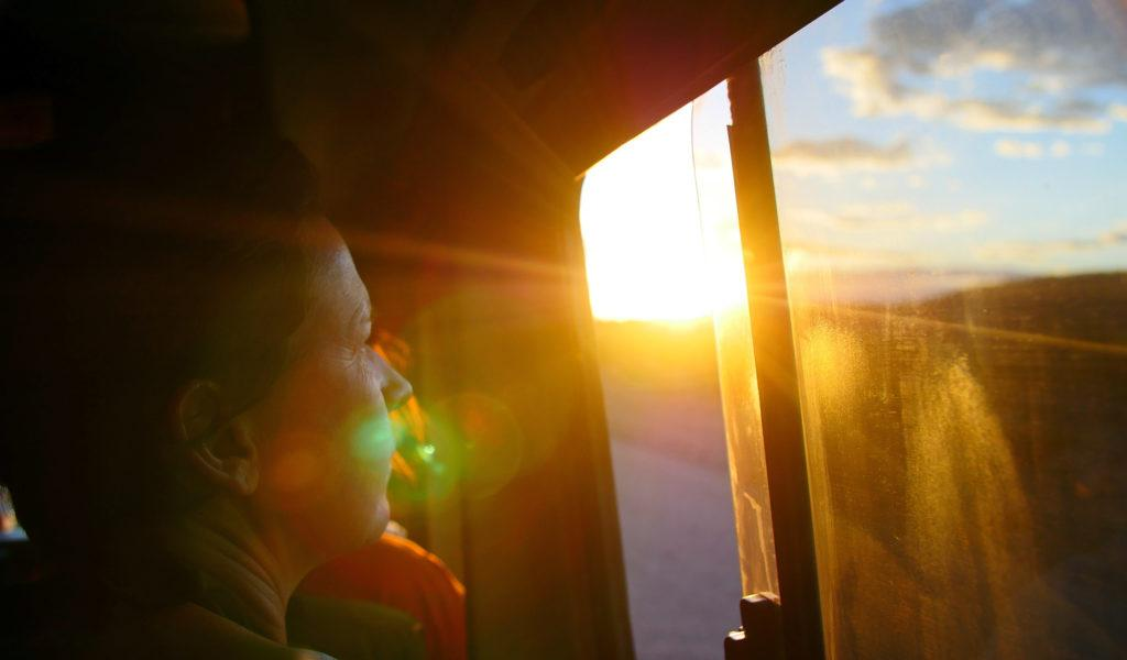 A woman looking out of the window of a tour vehicle while the sun shines on her face