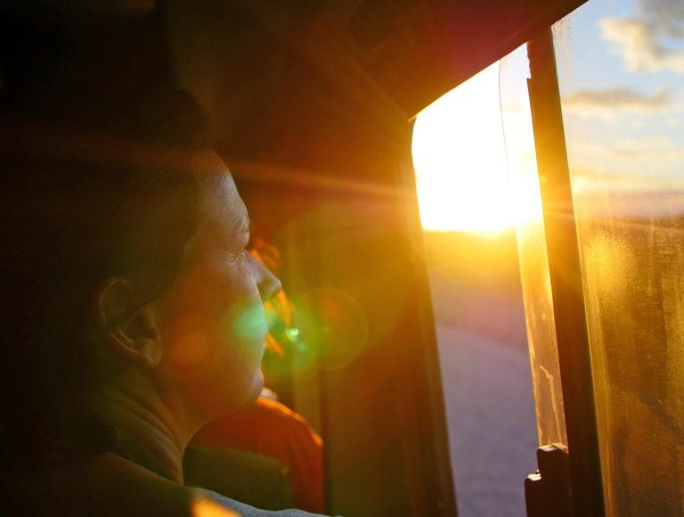 A woman looking out of the window of a tour vehicle, the sun shining on her face