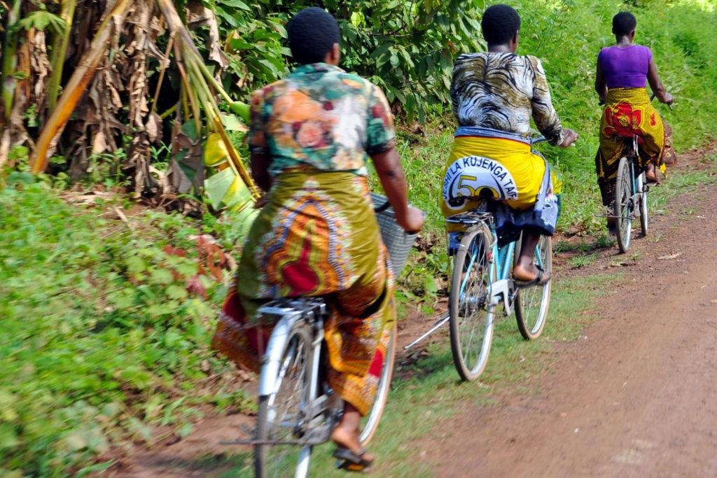 Three women riding on bicycles along a road in rural Tanzania